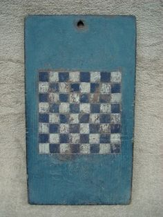 grrreat old painted checker board game board!! Squares painted dark blue/white on old blue background.  19 in long x 11 in wide x .375 in thick. Hole for hanging