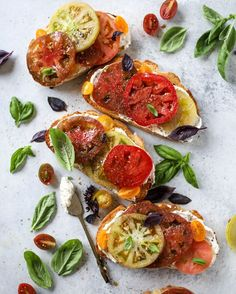 A favorite recipe for heirloom tomatoes on garlic toast that is spread with fresh basil whipped feta cheese! Topped with lots of salt, pepper and olive oil!