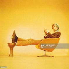 Photo of Scott WALKER; Scott Walker (Scott Engel) posed, studio, sitting on 1960s chair, solo era
