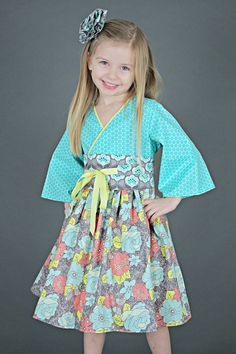 This aqua dress picks up the ocean breeze and brings sunny days with your angel where ever she goes. The aqua and coral flowers are scattered across the skirt of the dress making you dream of flower dreams. The dress has a full skirt making it perfect for twirling in the meadows. #flowergirl #birthday #toddlergirls