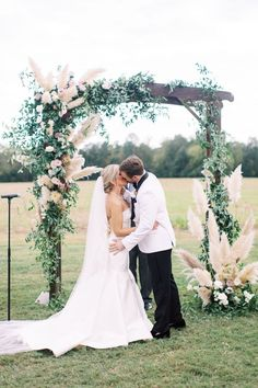 Lush greenery wedding arbor with greenery smilax, white, blush and mauve roses, pampas grass arch, boho and romantic archway, wedding ceremony, natural growing arbor floral installation, first kiss, Photographer: Nikki Santerre | Film Lab: Photovision | Stylist / Planner: The Blush Events | Floral Designer: Wild Fleurette | Dress Designer: Anne Barge | Rentals: Paisley and Jade | Venue: Burlington Plantation