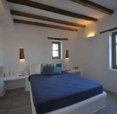 Built bed and night tables, decorative beams and window lintels. Smart lighting idea.