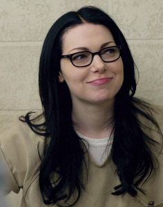 Laura Prepon pinkly smiling in black horn-rimmed eyeglasses & matching chestlength hair, V-neck pale shirt over white undershirt