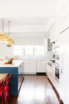 Dreamy kitchen with gold pendant lights and blue kitchen island