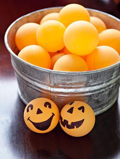 """""""Turn orange table-tennis balls into mini pumpkins for the pumpkin toss game (see the previous slide) by drawing pumpkin faces with permanent marker onto the sides."""""""