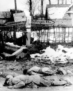 Dead American soldiers laying face down at a crossroad in Belgium, Dec 1944