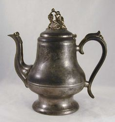 Description: A circa 1850s pewter coffee or teapot made by Morey & Obert Pewters of Boston Massachussetts. The pot has a circular flat bottom, having a circular foot, pedestal base rising to a constri