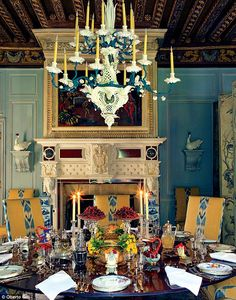 A table setting at the designer's Chateau de Wideville outside Paris: A painted tôle and porcelain eighteen-branch chandelier, by Meissen, hangs above the table. Each setting has its own silver-gilt salt throne