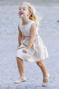 Delighted: Sticking her tongue out, the playful toddler ran towards her waiting mother