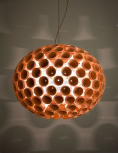 The ellipsoidal Terra Light is composed of 190 terracotta flowerpots. These flowerpots are secured to the perimeter of a white powder-coated sheet metal frame by their existing drain hole. The light from a single bulb radiates outward from the center to illuminate both the inside and outside of each pot. The three-dimensional texture created by these iconic clay pots glows in a striking orange-red hue. The repetitive, cylindrical shapes of the flowerpots cast an unexpected, ethereal shadow…