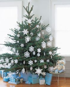 """This tree twinkles with a dusting of paper snowflakes; each is ironed flat to smooth out the folds, and hangs by a paper clip bent open to form an S. The beauty of paper snowflakes is that, even with slight imperfections, when they are massed together, they still elicit """"oohs"""" and """"ahhs.""""    Get the Snowflake Template"""