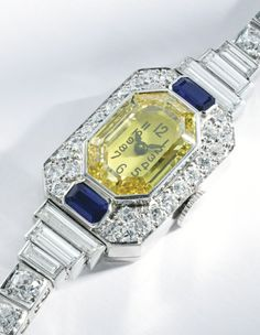PLATINUM, YELLOW DIAMOND, DIAMOND AND SAPPHIRE BRACELET-WATCH - The octagonal dial set with a cut-cornered rectangular portrait-cut Fancy Intense to Fancy Vivid Yellow diamond, with two emerald-cut sapphires, the dial and bracelet further set with round, baguette and old European-cut diamonds weighing approximately 6.25 carats, mechanical movement, length 6 1/8 inches, circa 1930.