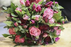 A seasonal, spring bouquet with red and pink hues made by McQueens. Perfect for Mother's Day.
