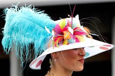Feather in her cap: A spectator wears a fancy hat while walking through the paddock area by © Mark Humphrey/AP via msn.foxsports.com