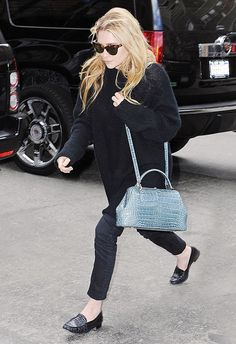 Ashley Olsen combines reptile with black crocodile loafers and a colored bag.