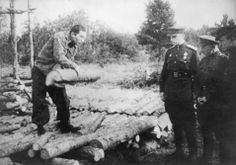 Klooga, Estonia, Avraham Aaronson demonstrating to Soviet officers the method used by the Germans for burning the bodies.