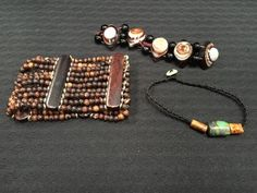 ETHNIC LOT OF JEWELS INCLUDES A WIDE STAINED BONE BEADED BRACELET, STONE BEADED BRACELET THAT APPEAR TO BE EYES OR SNAIL SHELLS AND A TURQUOISE NATURAL BARREL BEADED BRACELET.