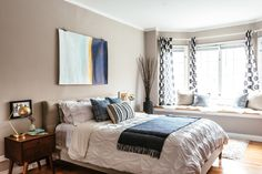 The master bedroom is the couple's relaxing oasis. The Pintuck Duvet is West Elm.