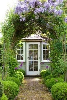 Archway with wisteria leading to summerhouse
