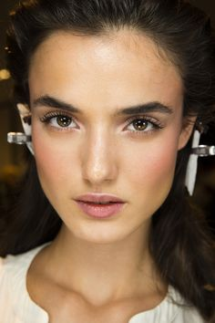 VersacePat McGrath gave models a pretty, pink-toned beauty at Versace, with a dusting of rosy shimmer on the eyes and cheekbones, offset by bold brows.