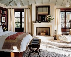 Cindy Crawfords bedroom has a wonderfully soft warm feeling to it with the creamy tones of  the walls & curtains & the luxurious rugs to the contrast of the dark wood & the red & gold bed throw. I love the chaise, I could imagine being curled up there with a book with the fire burning. Its both cosy & elegant.