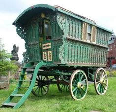 Beautiful seafoam green gypsy caravan trailer with intricate scrollwork detailing at the entrance.