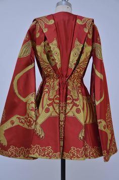 Heavy scarlet and yellow gazar, woven with heraldic beasts, the wide gothic sleeves attached to the lower skirt sides. Alexander McQueen cape has a kimono collar that extends to back V-shaped panel, batwing sleeves with cutout detail, pleats through back . Concealed snap fastenings at front. Fabric :100% silk; lining: 100% silk.