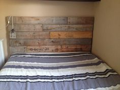 head board made from recycled wood from large electric cable reels. We put them through the thickness planer first to take the roundness out of them then arranged accordingly and put braces on the back. then attached to the wall. the numbers from the reels added interest. Needed a couple more.