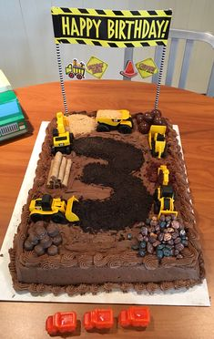 Carter's Construction Cake! Got a sheet cake from Costco, chocolate candies from Winco's bulk bins. The 3 is crushed Oreo, the sand is graham cracker. Construction vehicles were $5.99 at Target. Sign and candles from Hobby Lobby. You can't mess this up!