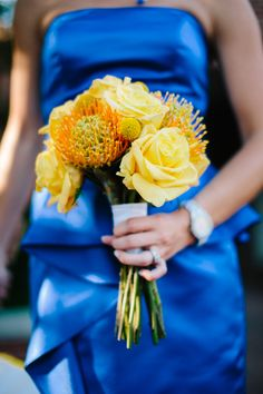 yellow bouquet, and blue bridesmaid dress