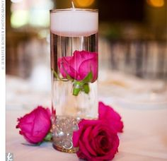 This would be super cheap and simple. You would just have to buy  a dozen roses and floating candles. The vases are at the dollar store right now. I don't like the stones in this one but it's simple and pretty. imagine a light pink rose...From weddingbycolor.com
