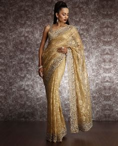 Complement your personal style by draping this lovely gold lace saree enriched with swarvoski