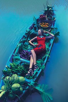 Eniko Mihalik on a floating boat filled with fruits and vegetable in Vietnam for Anthropologie l #travel #fashion