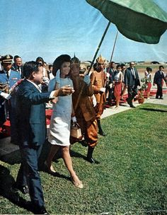 At her arrival in Cambodia, Jackie is escorted by Prince Sihanouk and a royal umbrella bearer. 1967. Photo: Life Magazine Archive.