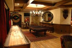 Luxurious game room with pool table and shuffleboard, in a Tuscan style home with rustic flair.