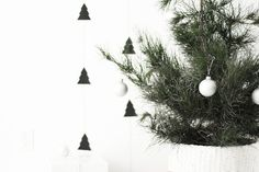 Kristi Murphy made this minimal garland using a Cricut and a tree template, but you could make your own with scissors or an X-acto knife if you have skills. Also, a paint-dipped basket makes for a chic tree stand.