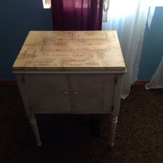 Vintage Singer Sewing Machine and cabinet painted in antique white with vintage sewing pattern decoupaged on top