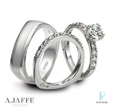 A. Jaffe platinum and diamond engagement ring with round brilliant side-stones and matching platinum wedding bands.