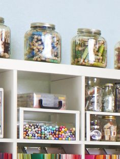 Ribbon pieces that are shorter than a yard and a half go in 8-inch glass jars from World Market and are organized by color. Regina wraps them around wood doll pins from Hobby Lobby and secures each piece with a rubber band.
