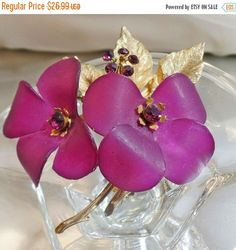 This #vintage plum purple flower blossoms brooch is stunning!  It features a two four petal plum purple flowers of celluloid with purple rhinestone centers and a purple rhin... #ecochic #etsy #jewelry #jewellery