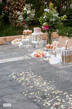 Floral themed wedding welcome table with sweets and flowers.