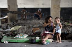 A mother feeds her baby at an underpass in Manila on August 28, 2014 near where informal settlers' homes were recently demolished. The Philippine economy rebounded to post 6.4-percent growth in the second quarter and regain its status as one of the strongest in Asia, authorities said on August 28. Officials said in April that amongst their new targets is the lowering of the country's poverty incidence from 25.2 percent of the population in 2012 to 18.0 to 20.0 percent by 2016.