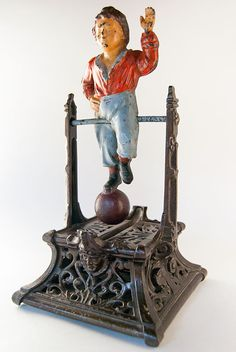 Boy on Trapeze Antique Cast Iron Mechanical Bank »  Circa 1888: Originally christened French's Automatic Toy Bank, the Boy on Trapeze is the single mechanical bank produced by Philadelphia, Pennsylvania's J. Barton Smith Company. This beautiful and elegant bank works by placing a coin in the acrobat's chapeau.