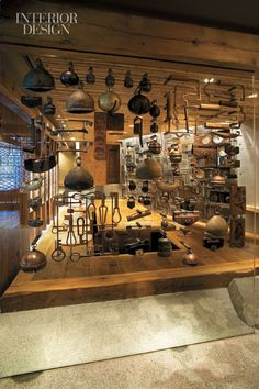 Antique tools hang from metal bolts supported by a panel of glass.