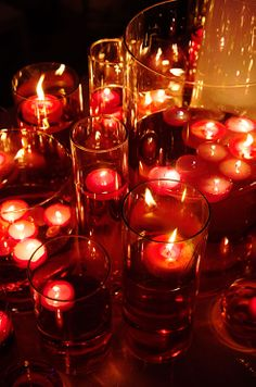 SO pretty.Groups of red floating candles in various sized hurricanes exude a romantic glow.