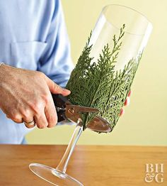 This DIY Evergreen Candle Will Make Your Holidays Even Brighter - - Take a pretty glass container, glue bits of greenery around it, and set candles inside to combine the freshness of greenery with the welcoming warmth of candlelight. Country Christmas Decorations, Easy Christmas Crafts, Farmhouse Christmas Decor, Christmas Centerpieces, Homemade Christmas, Rustic Christmas, Xmas Decorations, Diy Christmas Wedding, Tree Branch Centerpieces