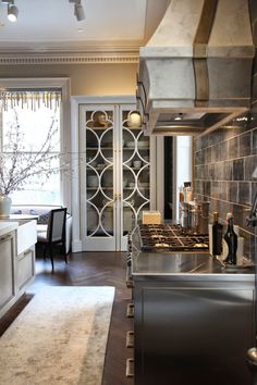 Love the tall cabinet/closet with decorative doors. Can't tell if its a built in or freestanding piece, but it's cool.