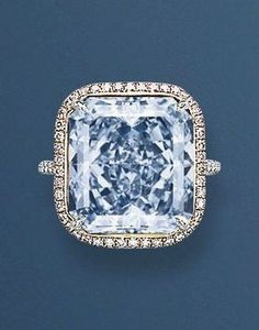 AN EXTRAORDINARY COLOURED DIAMOND RING Set with a rectangular-cut fancy intense blue diamond weighing 13.39 carats, to the micro pavé-set fancy pink diamond surround and diamond bifurcated hoop, mounted in platinum and 18k white gold