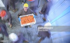 Stock Photo : Portrait of worker holding basket of smoked salmon fillets in busy…