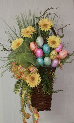 Easter basket is full of colorful sparkly Easter eggs, along with yellow daisies, grasses, twigs, vines and a double bow made of lime green poly mesh ribbon and a yellow plaid ribbon. Wreaths For Front Door, Door Wreaths, Spring Crafts, Holiday Crafts, Easter Wreaths, Christmas Wreaths, Ikebana, Diy Ostern, Easter Colors